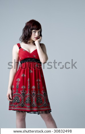 Beautiful young retro woman modeling in a red paisley print dress #30832498