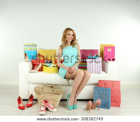 Woman with shopping bags and shoes on sofa in room #308382749