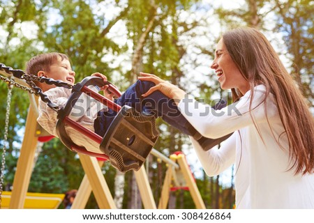 happy mother pushing laughing son on swing in a park Royalty-Free Stock Photo #308426864