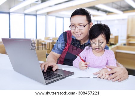Male tutor typing on the laptop computer while teaching little girl to write, shot in the classroom #308457221