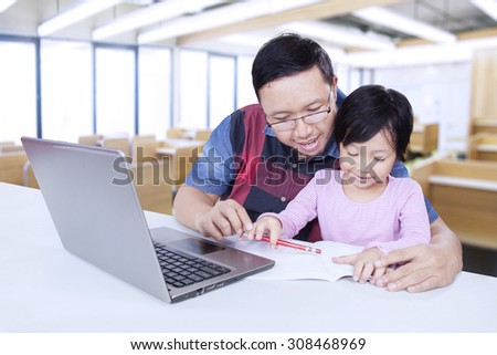 Lovely female elementary school student studying with male teacher in the classroom, using a book and laptop on the table #308468969