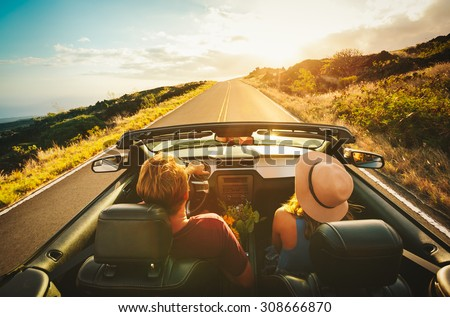 Happy Young Couple Driving Along Country Road in Convertible at Sunset Royalty-Free Stock Photo #308666870