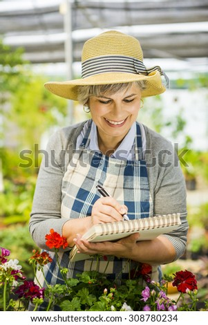Mature woman in a greenhouse taking notes on a notebook #308780234