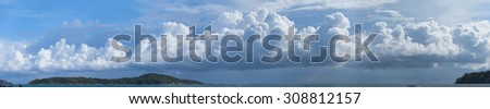 Beautiful panoramic photo of huge, billowing storm clouds, building and forming over the tropical sea near a popular tourist beach.