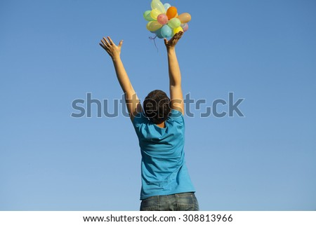 Young woman with colorful balloons in summer field #308813966