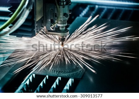 CNC Laser cutting of metal, modern industrial technology. Small depth of field. Warning - authentic shooting in challenging conditions. A little bit grain and maybe blurred. #309013577