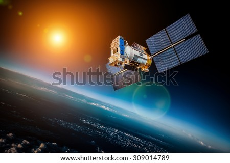 Space satellite orbiting the earth on a background star sun. Elements of this image furnished by NASA. Royalty-Free Stock Photo #309014789