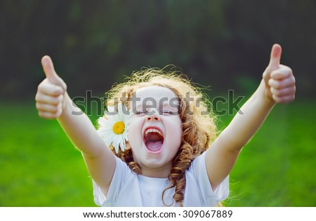 Laughing girl with daisy in her hairs, showing thumbs up. Royalty-Free Stock Photo #309067889