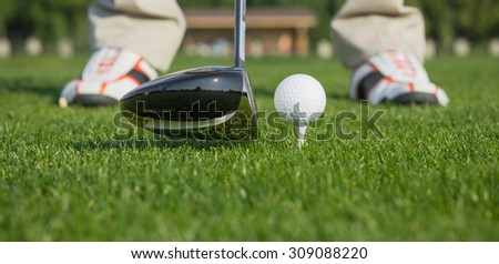 Close-up picture of golf ball behind driver at driving range, plenty of copy-space and very shallow depth of field.