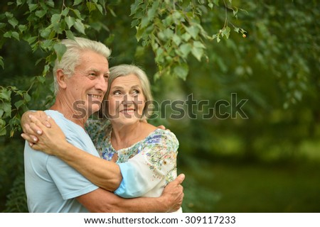 Loving mature couple on a walk in the park in summer #309117233