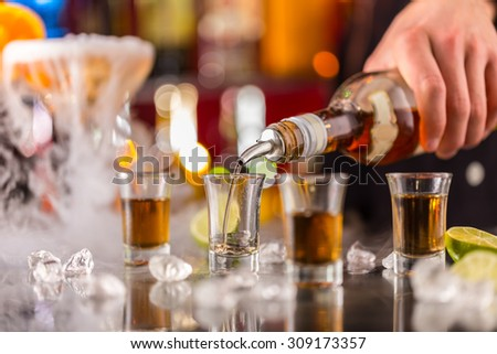 Barman pouring hard spirit into glasses in detail #309173357