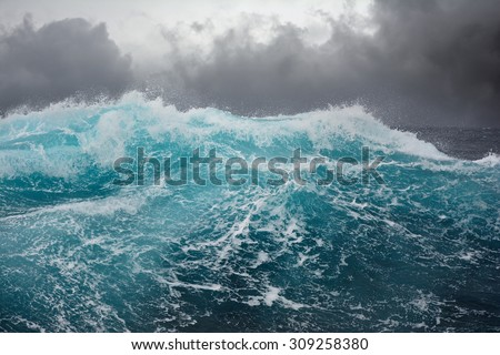 Dark clouds and crashing ocean waves during storm in the atlantic ocean Royalty-Free Stock Photo #309258380