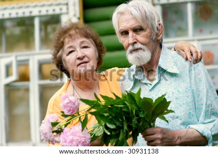 Elderly husband and wife hold flowers in hands and laugh and joke against house. #30931138