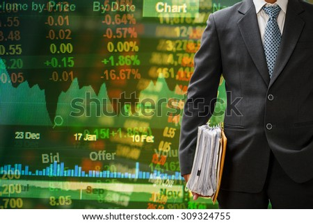 investor holding files on stock market board background
