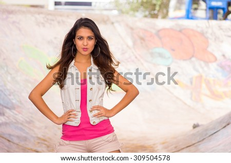 Brunette model wearing pink top, white vest and shorts standing inside concrete skatepark posing for camera. #309504578