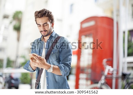 Young man using mobile phone in street #309541562