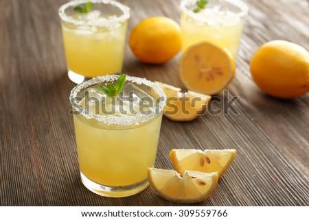 Glasses of lemon juice on wooden table, closeup #309559766
