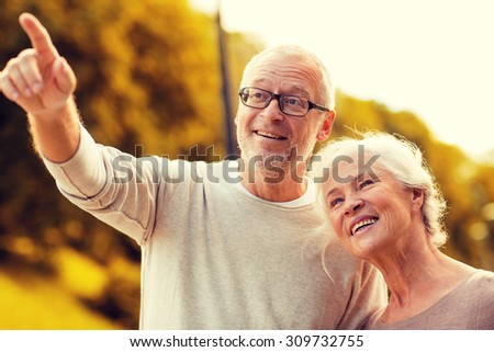 family, age, tourism, travel and people concept - senior couple pointing finger in park #309732755