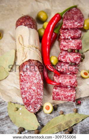 Salami on wooden background with spices #309755006