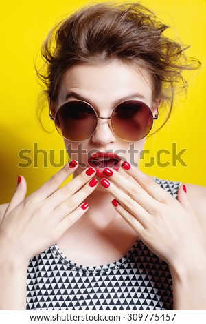 Portrait of a beautiful girl in round glasses on a yellow background in the studio posing surprise