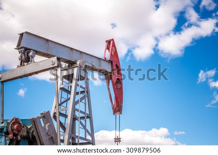 Oil pump in the open air, on a background of the cloudy sky #309879506