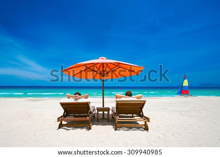 Couple on a tropical beach relax in the sun on deck chairs under a red umbrella.  Travel  background . #309940985