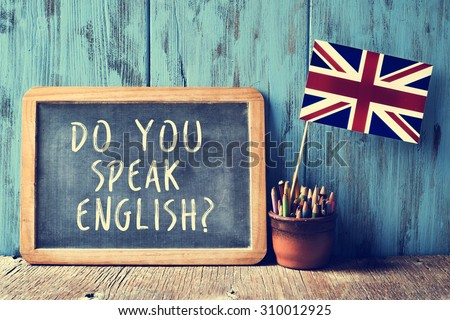 a chalkboard with the text do you speak english? written in it, a pot with pencils and the flag of the United Kingdom, on a wooden desk, with a filter effect Royalty-Free Stock Photo #310012925