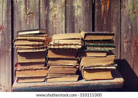 Piles of old books. Old books against an ancient wooden wall #310115300