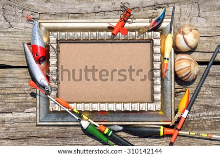 Wooden frame decorated with fishing tackle on a wooden background