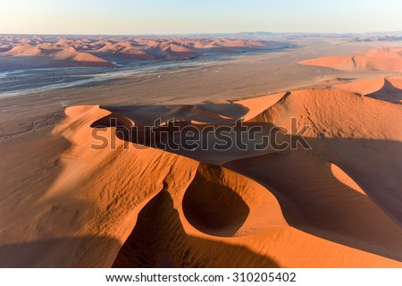 Aerial view of high red dunes, located in the Namib Desert, in the Namib-Naukluft National Park of Namibia. #310205402