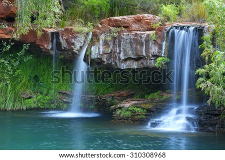 A small waterfall flowing into the Fern Pool in Karijini National Park, Western Australia.