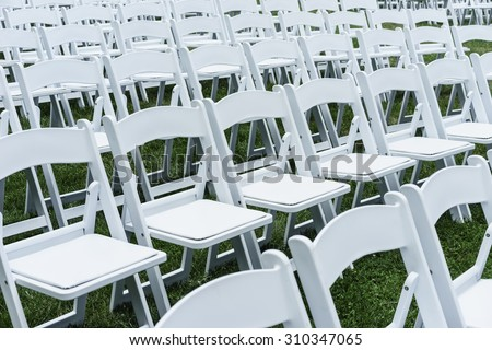 Symmetry of love: Rows of white folding chairs on lawn before a wedding ceremony in summer #310347065