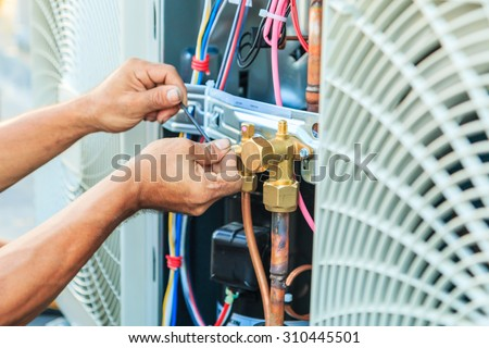 Air Conditioning Technician and A part of preparing to install new air conditioner.  Royalty-Free Stock Photo #310445501