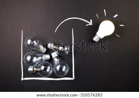 White light bulb glowing outside the drawing box, thinking outside the box or being different concept