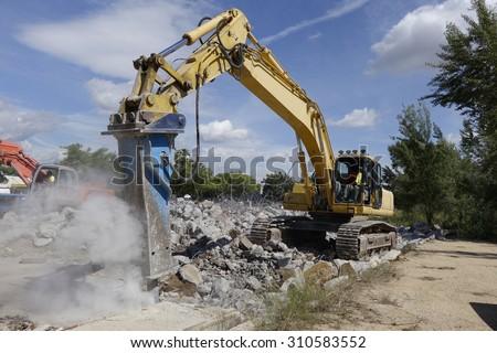 Big excavator with hammer, for concrete demolition                             #310583552
