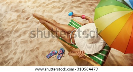 Vacation. Travel. Beautiful young woman relaxing on beach chair with cocktail. Top view #310584479