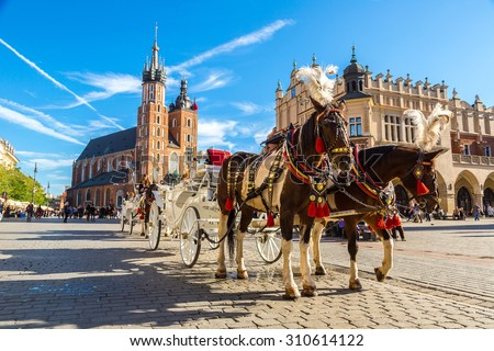 Horse carriages at main square in Krakow in a summer day, Poland Royalty-Free Stock Photo #310614122