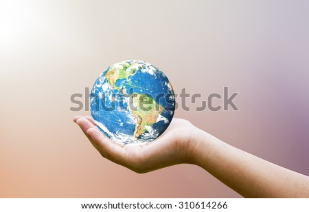 Female hands holding world on blurred sunset background with sun light : Elements of this image furnished by NASA #310614266