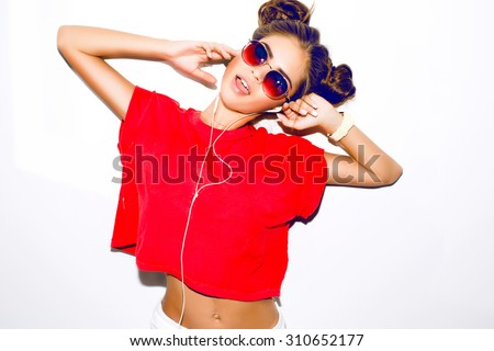 Indoor fashion autumn portrait of elegant sexy woman in luxury bright glamour outfit,red lips,red crop top and trendy sunglasses.Model holding earphones,listen music,ponytail.smiley woman,crazy,toned #310652177