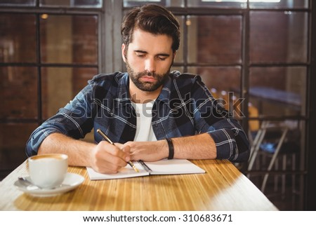 Young man taking notes in his notebook at a cafe #310683671