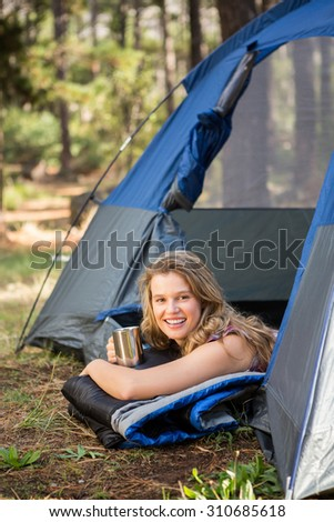 Portrait of pretty blonde camper smiling and lying in tent in the nature #310685618