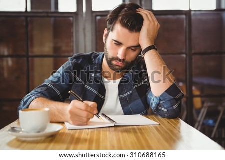 Young man taking notes in his notebook at a cafe #310688165