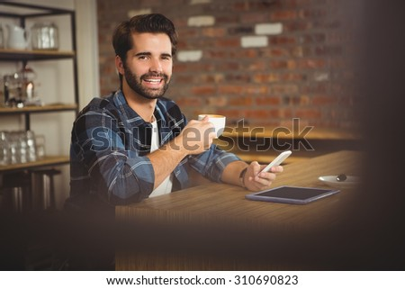 Young student using his smartphone in cafe #310690823
