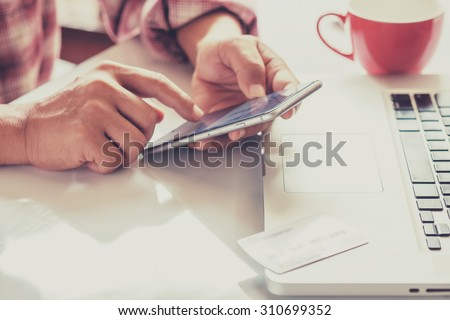 Man's hands holding a credit card and using smart phone for online shopping #310699352