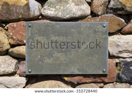 A blank, empty, slate sign plate on a stone wall with copy space and no writing.