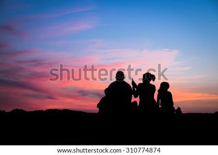 Silhouette of a family enjoying a beautiful sunset