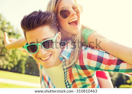 holidays, vacation, love and friendship concept - smiling teen couple in sunglasses having fun in summer park #310810463