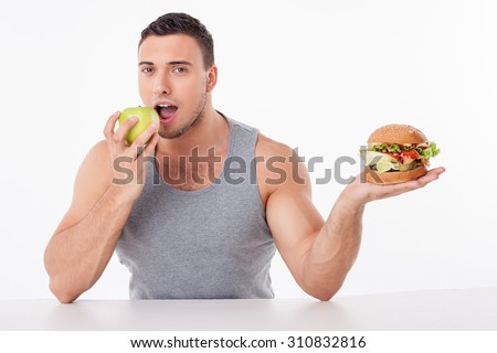 Handsome man is holding hamburger and apple. He is biting fruit with pleasure. He did right choice. Isolated on background #310832816