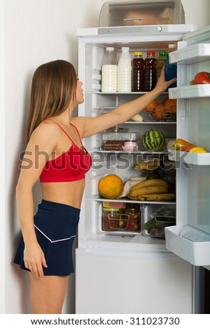 Woman standing by the fridge and choosing products #311023730