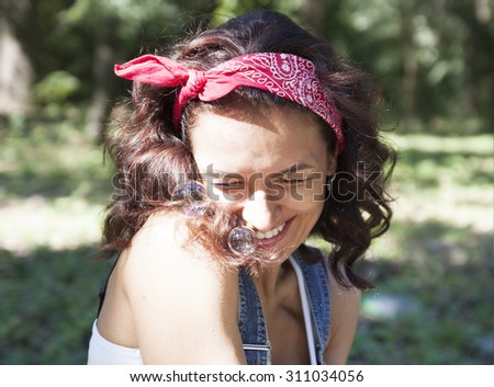 Young girl blowing soap bubbles outdoors #311034056
